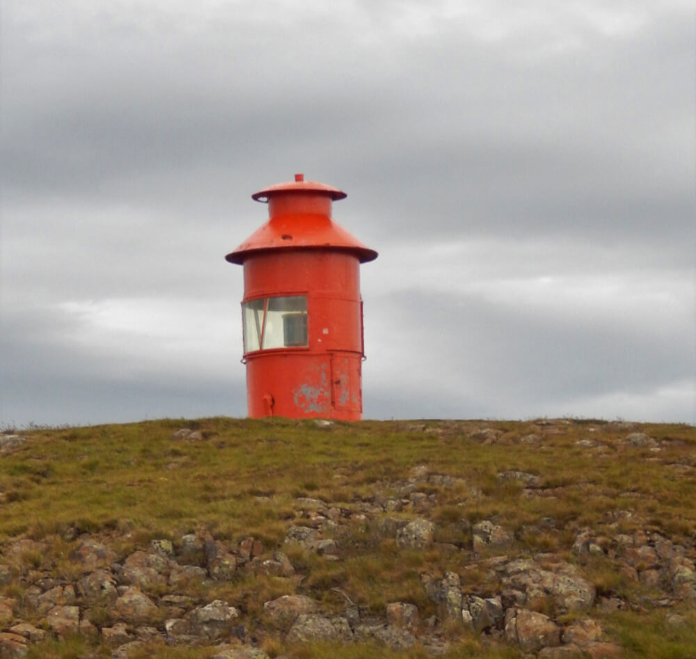 A small, red lighthouse sitting atop Súgandisey Island
