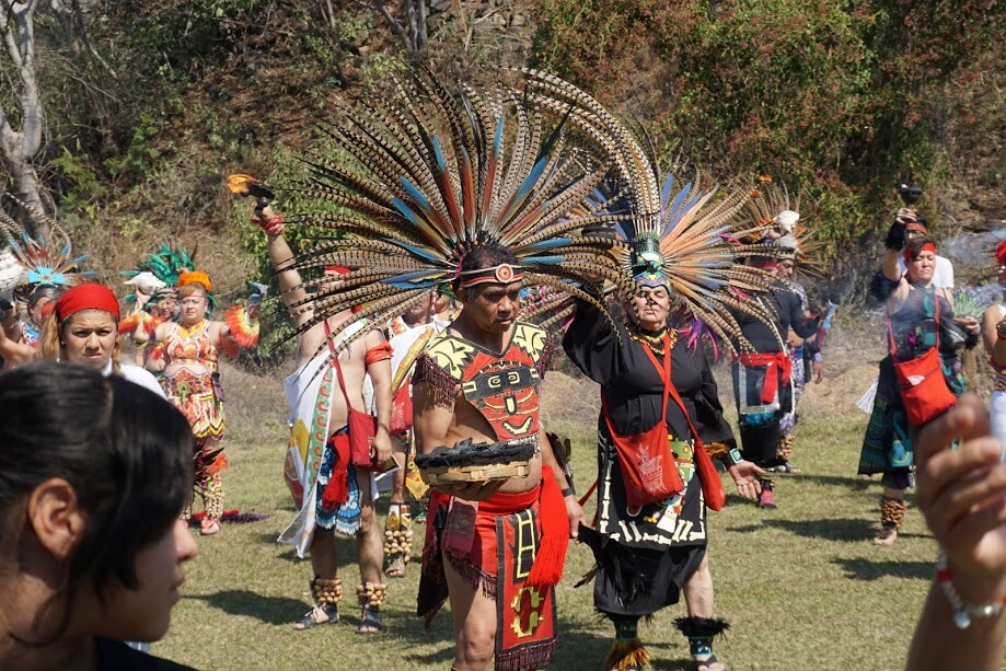 A group of dancers in colorful attire and feather headdresses re-enact an Aztec ceremony honoring the eagle god.