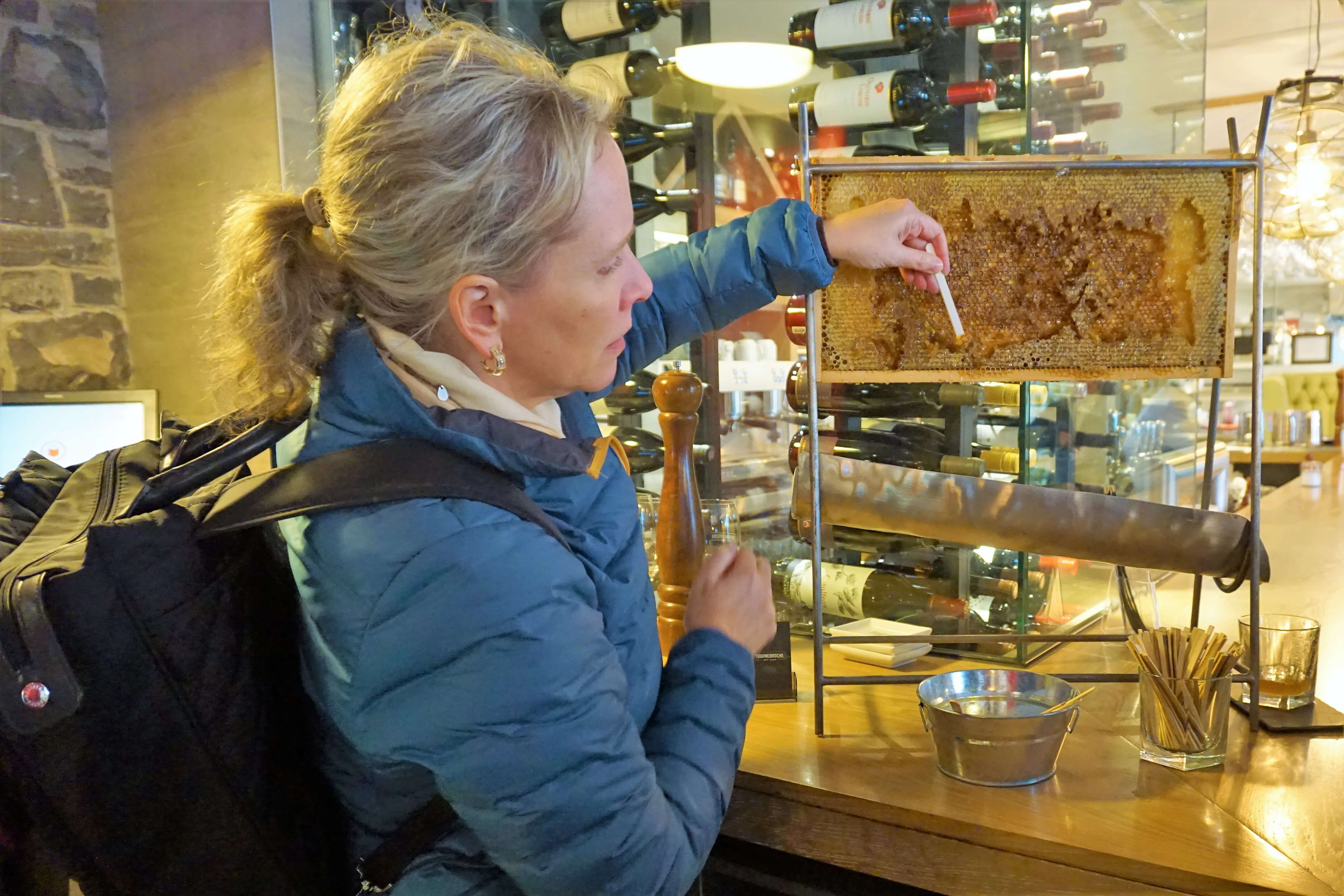 Sampling honey directly from the beehive at Tournebroche
