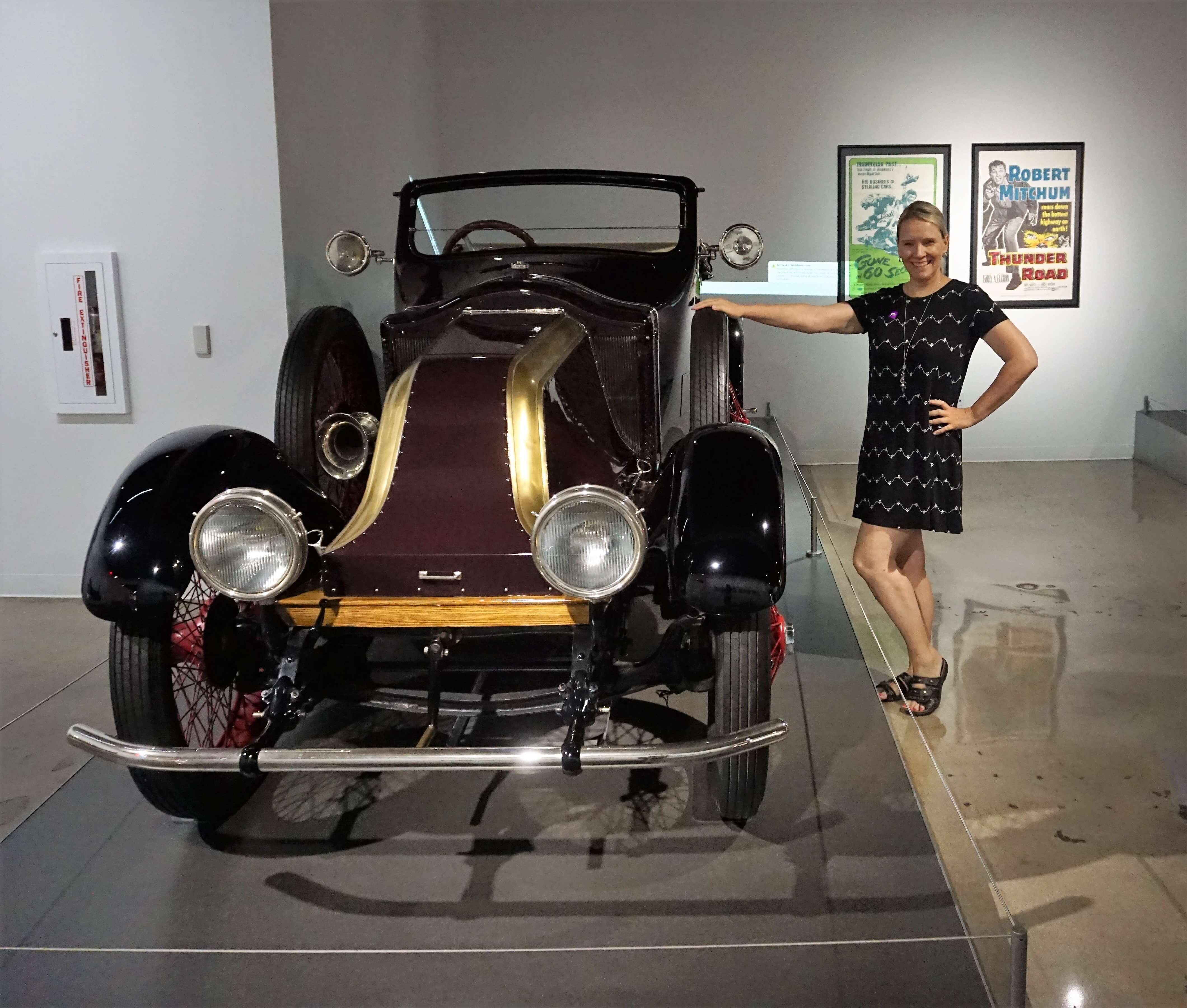 Wendy posing with one of the historic cars at The Petersen Automotive Museum