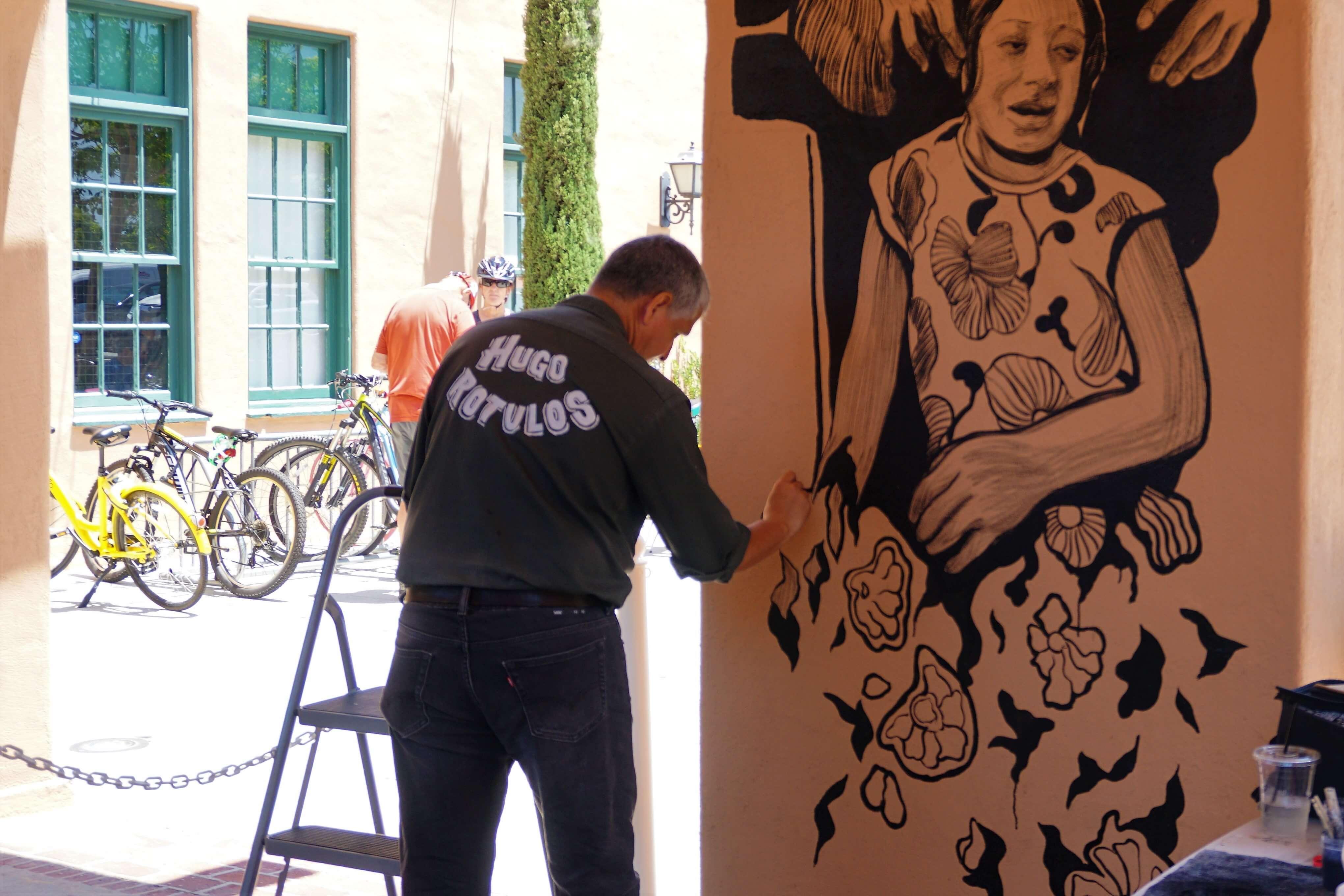 Artist Hugo Crosthwaite painting a mural outside Liberty Public Market