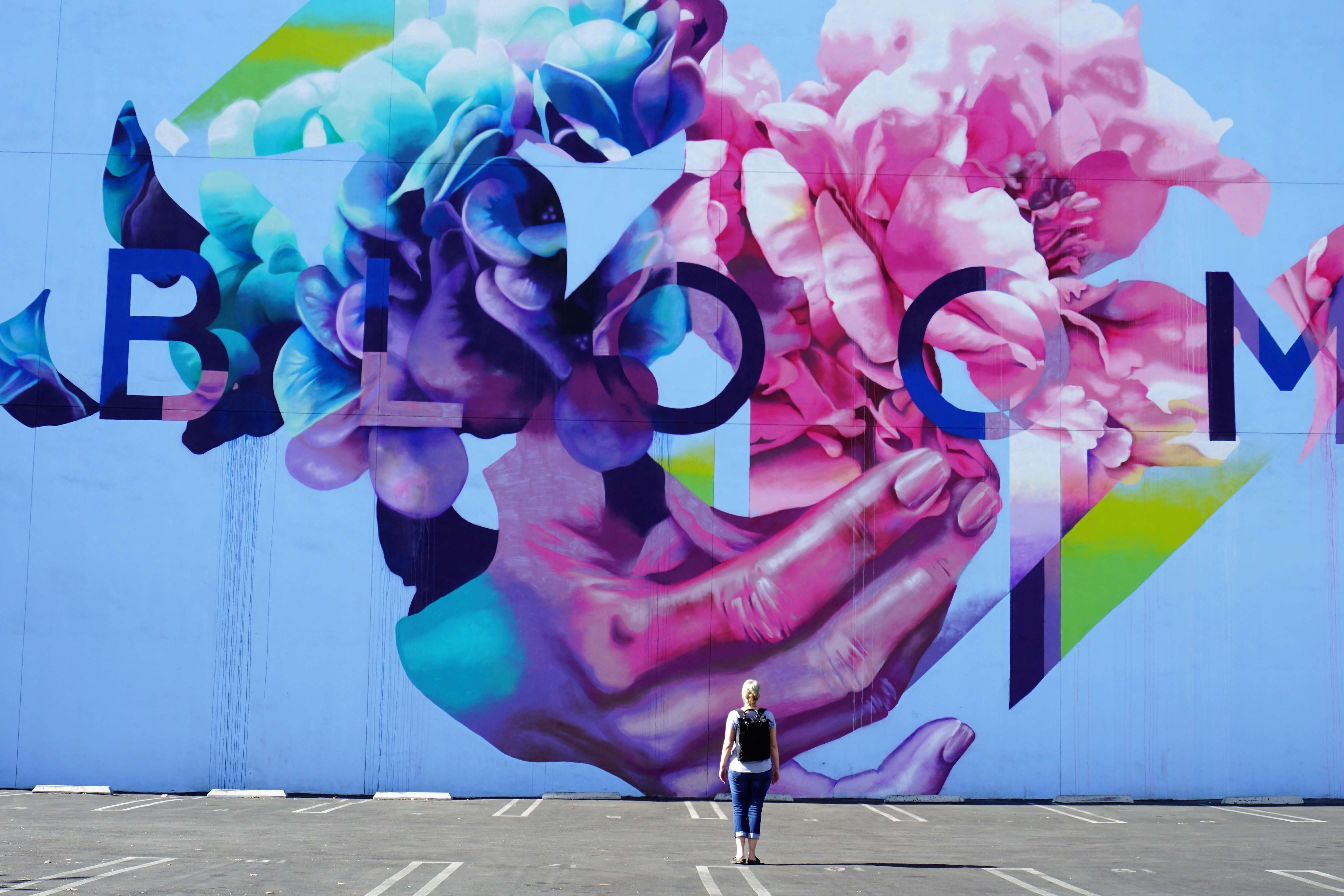 Wendy standing in front of the famous street mural, Bloom