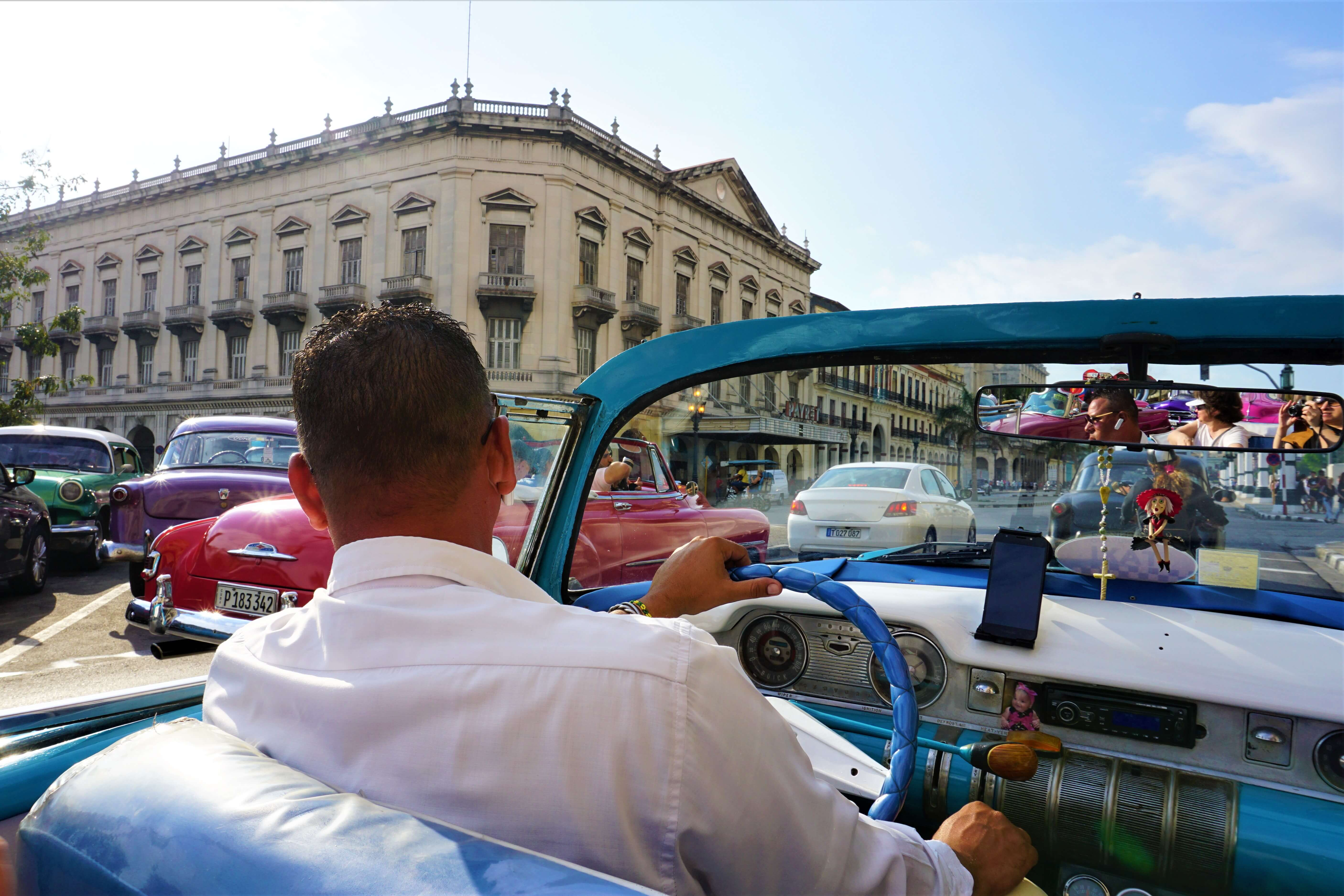 Back seat view of classic car tour in Havana