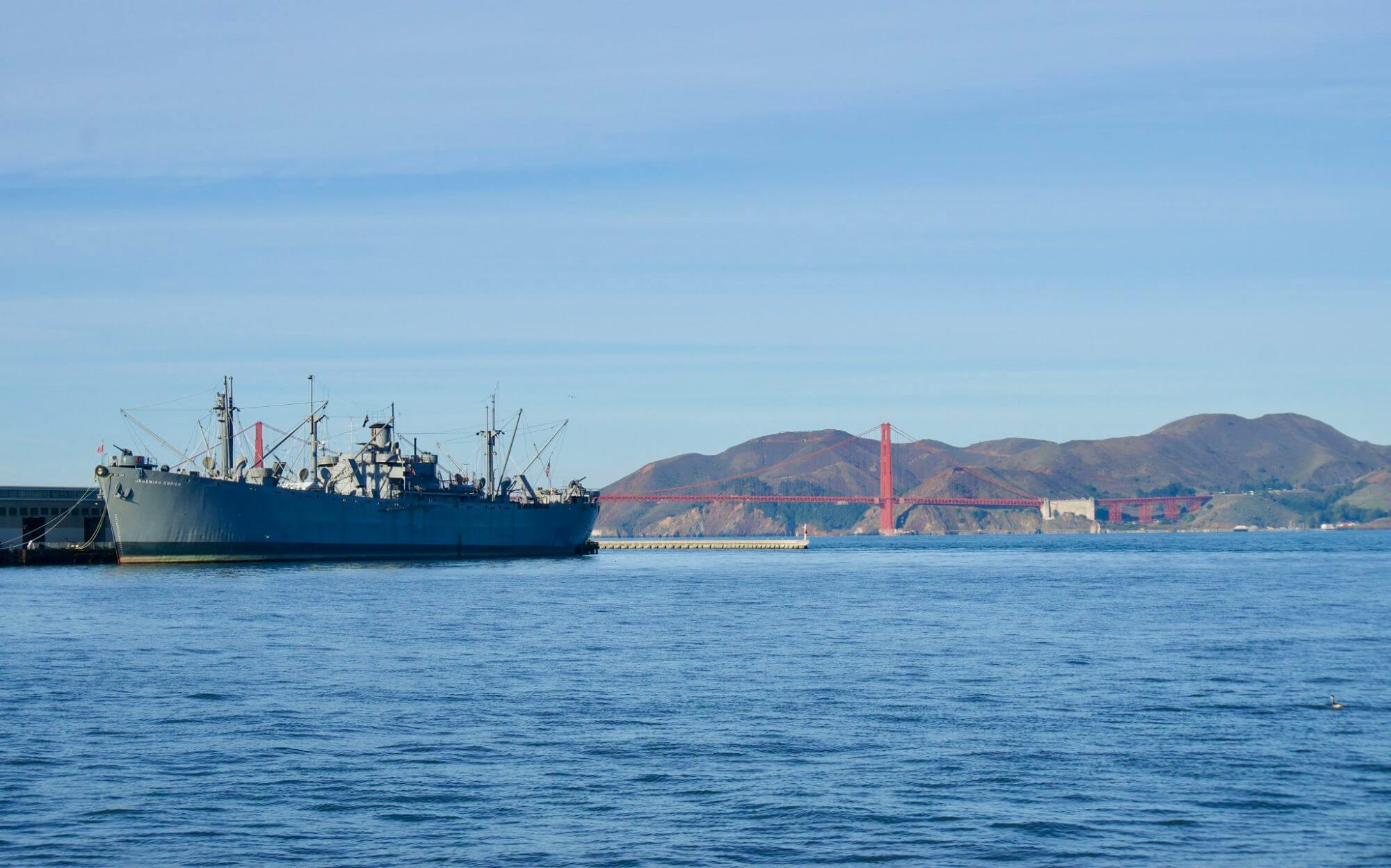 A naval boat in San Francisco Bay with Golden Gate Bridge in the distance