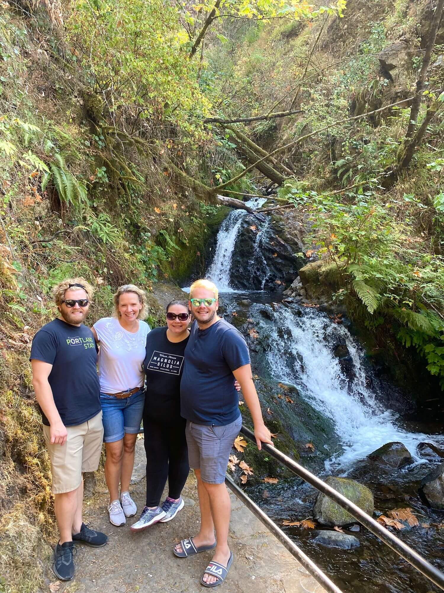 Four people in front of a waterfall